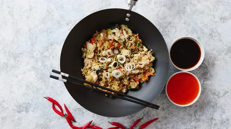 green peas : Delicious fried rice with chicken. Prepared and served in a wok with soy and sweet sour souces on side. Placed on stone background. Top view. Stock Footage