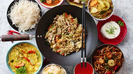 yum yum : Chinese food set. Chinese noodles, fried rice with chicken, tom yum soup, spring rolls, deep fried fish and udon. Top view. Asian style food concept composition. Stock Footage