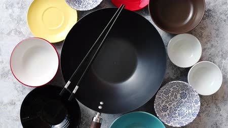 кухонная посуда : Traditional empty black iron wok pan placed on stone background with colorful ceramic bowls on side. Top view.