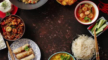 yum yum : Asian food set. Noodles, fried rice with chicken, tom yum soup, spring rolls, deep fried fish and udon with prawns. Top view on dark rustic background. Oriental style food circle composition.