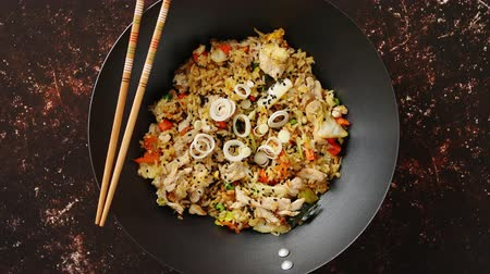 kínai evőpálcikák : Delicious fried rice with chicken. Prepared and served in a wok with soy and sweet sour souces on side. Placed on dark rusty background. Top view.