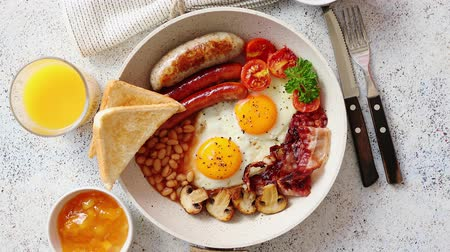 foods : Traditional Full English Breakfast including sausages, grilled tomatoes, mushrooms, eggs, bacon, baked beans and bread. Coffee and orange juice on sides. Top view.