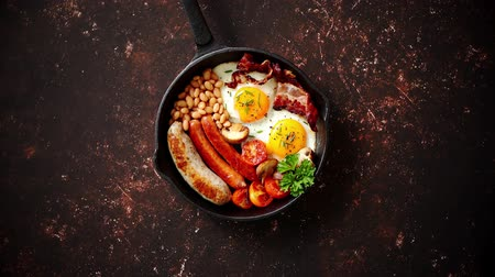 villa : English breakfast in iron cooking pan with fried eggs, sausages, bacon, beaked beans on dark rusty background.