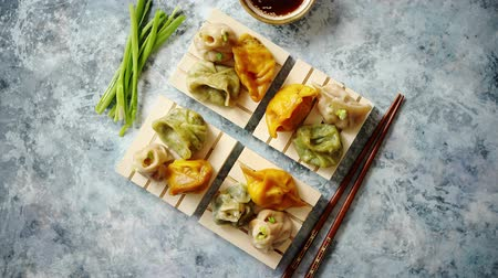 bamboo steamer : Delicious mixed kinds of chinese dumplings served on wooden stands with chopstick and soy sauce. Placed on stone background with copy space.