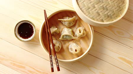 bamboo basket : Traditional chinese dumplings served in the wooden bamboo steamer over raw wooden background table. Top View composition. Stock Footage