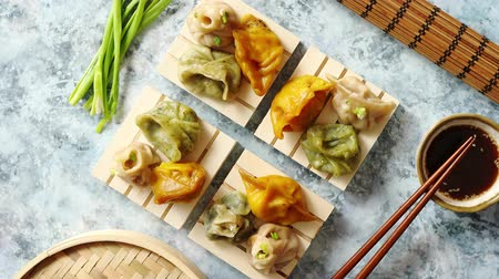bamboo basket : Delicious mixed kinds of chinese dumplings served on wooden stands with chopstick and soy sauce. Placed on stone background with copy space.