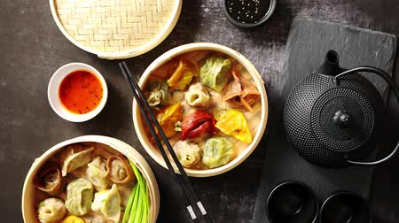 bamboo steamer : Composition of chinese food. Mixed kinds of dumplings from wooden bamboo steamer. Served with soy and spicy sauces and traditional tea in iron pot. Stock Footage