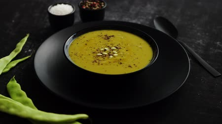 zupa groszek : Healthy food. Creamy soup with green bean in a ceramic black bowl on a dark rustic table. The concept of diet eating. Wideo