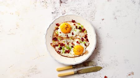 cebolinha : Two fresh fried eggs with crunchy crisp bacon and chive served on white ceramic plate. Fork and knife on side. Top view.