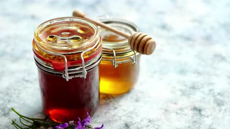 meruňka : Jars with different kinds of fresh organic honey placed in a row on a blue stone background Dostupné videozáznamy
