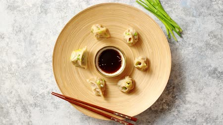 bamboo steamer : Delicious chinese dumplings served on wooden plate with chopstick and soy sauce in the middle. Placed on stone background with copy space. Chive od side. Stock Footage
