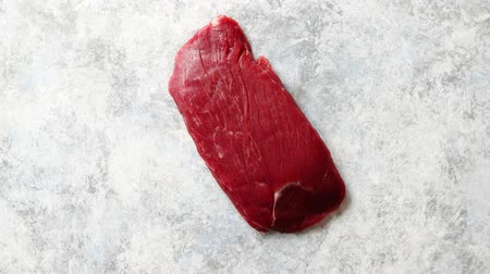 вырезка : Piece of raw fresh beef steak placed on gray stone background. Top view. Стоковые видеозаписи