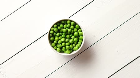 pea pods : Fresh green pea seeds in a white ceramic bowl. Shot from above. Placed on wooden table with copy space. Stock Footage
