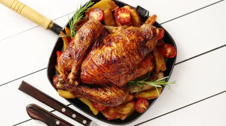 chicken recipes : Roasted whole chicken in cast iron black pan. With potatoes, tomatos and rosemary herb. Placed in white wooden table. View from above. Shot with copy space.