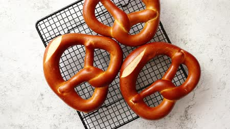 pretzel : Three german fresh baked pretzel buns placed on steel grill frame. Stone background. Shot from above.