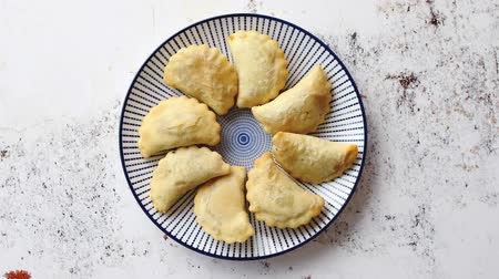 pierogi : Hot and tasty deep fried polish dumplings with meat filling sprinkled with fresh pepper. Placed on a blue ceramic plate. Top view on rusty white background with copy space