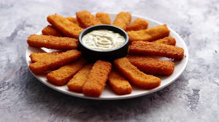 треска : Crumbed fish sticks served with garlic dip sauce on a white plate on a stone table. Top view with copy space.
