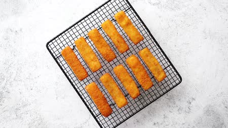 rántott : Rows of golden fried fresh fish fingers fillets placed on black grill. Ready for meal. Stone background.