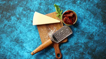 ralado : Grated parmesan cheese and metal classic grater placed on wooden cutting board. Dried tomatoes on side. Blue background. View from above.