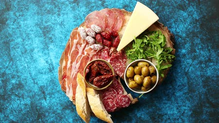 вылеченный : Delicious mix of different snacks and appetizers. Spanish tapas or italian antipasti on a wooden plate. View from above. Placed on blue table. Стоковые видеозаписи