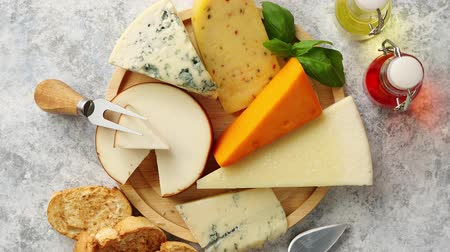cheese types : Various types of cheese served on rustic wooden board. Placed on concrete background. Stock Footage