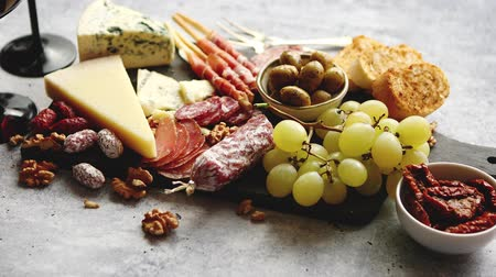 przekąski : Antipasto platter cold meat and cheese board with grapes, wine, various kinds of cheese, grissini bread sticks on white rustic background. View from above