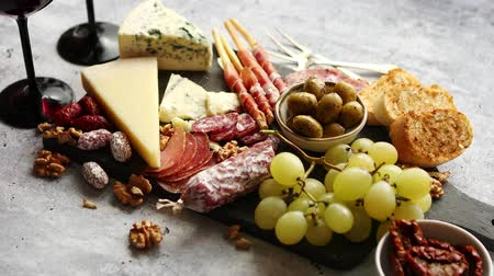 antipasti : Antipasto platter cold meat and cheese board with grapes, wine, various kinds of cheese, grissini bread sticks on white rustic background. View from above