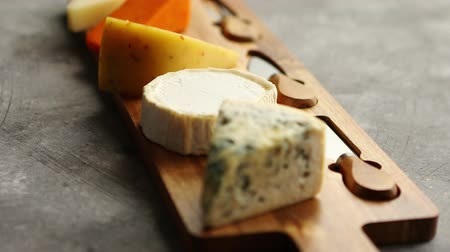 cheese types : Assortment of various kinds of cheeses served on wooden board with fork and knives. Placed on concrete background. Stock Footage
