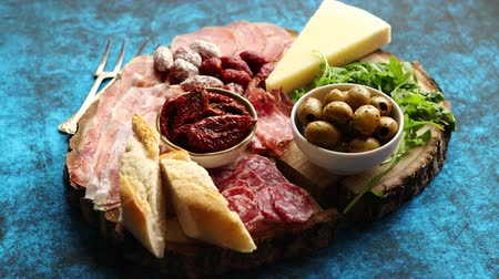 cheese slice : Delicious mix of different snacks and appetizers. Spanish tapas or italian antipasti on a wooden plate. View from above. Placed on blue table. Stock Footage