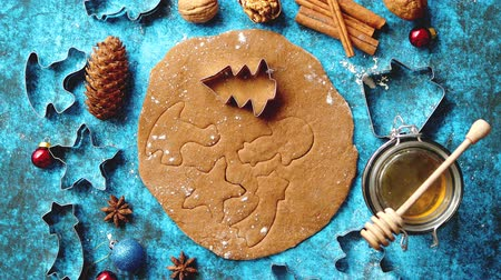 pastry ingredient : Christmas baking concept. Gingerbread dough with different cutter shapes and spices on sides. Top view on blue rustic background. Stock Footage