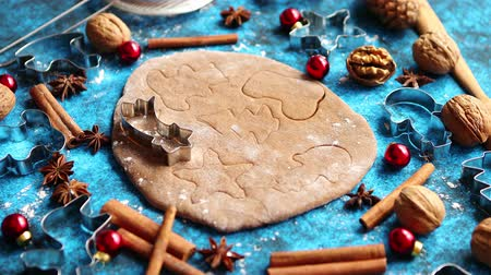 anis : Christmas baking concept. Gingerbread dough with different cutter shapes and spices on sides. Top view on blue rustic background. Vídeos