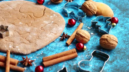 anýz : Christmas baking concept. Gingerbread dough with different cutter shapes and spices on sides. Top view on blue rustic background. Dostupné videozáznamy