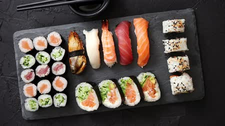 yılanbalığı : Sushi rolls set with salmon and tuna fish served on black stone board. Top view of traditional japanese cuisine. Asian food on black stone slate with chopsticks.