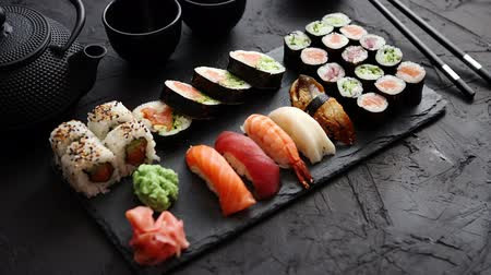 slate : Assortment of different kinds of sushi rolls placed on black stone board. Traditional asian iron tea pot on side. Top angle view.