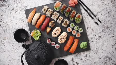 arduvaz : Assortment of different kinds of sushi rolls placed on black stone board. Traditional asian iron tea pot on side. Top angle view.