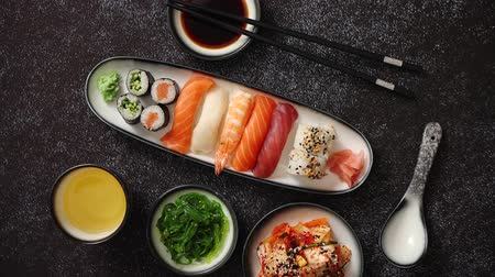 gunkan : Asian food assortment. Various sushi rolls placed on ceramic plates. Kimchi and goma wakame salads. Soy souce and chopsticks on sides. Grungy dark background with copy space.