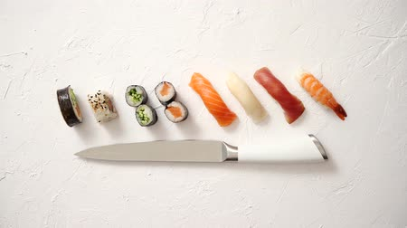 arduvaz : Various sushi rolls with Japanese knife on white stone slate background. With copy space for text. Top view. Stok Video