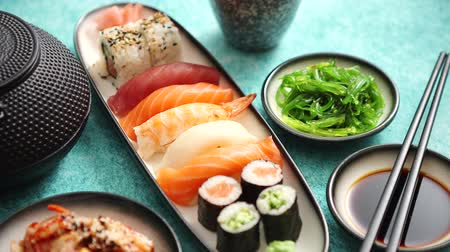 yılanbalığı : Various sushi rolls placed on ceramic plates. Traditional iron tea pot and green tea in cup. Kimchi and goma wakame salads. Soy souce and chopsticks on sides. Blue background.