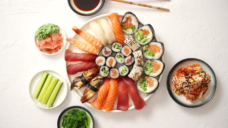 california rolls : Asian food assortment. Various sushi rolls placed on round ceramic plate. Kimchi and goma wakame salads, fresh cucomber, ginger and wasabi. Soy souce and chopsticks on sides.