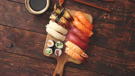 serving board : Sushi Set. Different kinds of sushi rolls on wooden serving board with soy sauce and chopsticks over dark wooden texture background. Top view with copy space.