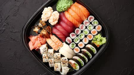 gunkan : Japanese food concept. Catering, various kinds of sushi on plate or platter set. Chopsticks, ginger, soy sauce, wasabi. Placed on stone black background in plastic delivery box. Stock Footage