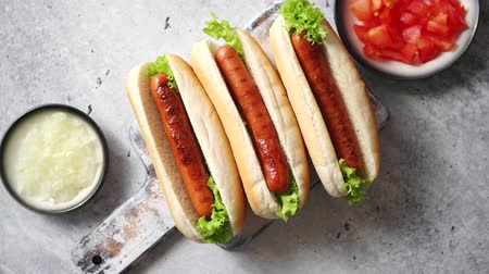 párek v rohlíku : Three barbecue grilled hot dogs with sausage placed on wooden cutting board. Bowls with tomato and onionon sides. Traditional american fast food. Above angle view.