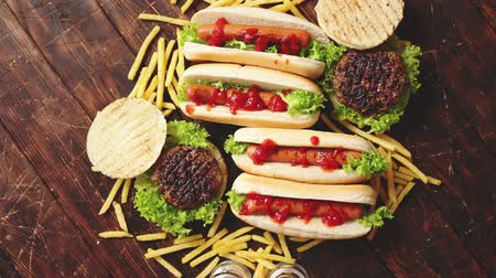 párek v rohlíku : Fastfood assortment. Hamburgers and hot dogs placed on rusty wood table. Served with french fries. View from above.