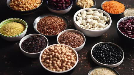 curcuma : Various superfoods in smal bowls on dark rusty background. Superfood as rice, lentil, beans, peas, goji, flaxseed, buckwheat, couscous, chickpeas Above view Flat lay