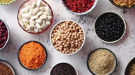 peas : Organic superfood assortment in bowls. With raw peas, beans, wild rice, lentil, Goji berries, cranberry, couscous, linseeds on white rusty background. Above view. Stock Footage