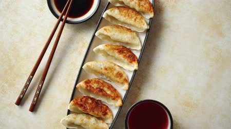 клецка : Orginal asian dumplings gyoza served in long plate with soy souce in a bowl and a cup of tea. With chopsticks. Placed on rusty background.