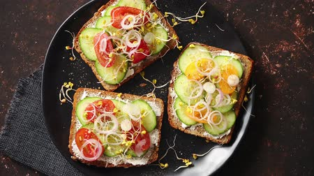 хлеб : Vegetable toasts. Healthy toasts with cucomber, cherry tomatoes, crumbled feta cheese and radish sprouts on a black plate. Table top view. Dark rusty background.