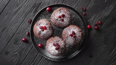 vdolky : Fresh and tasty chocolate muffins served on blac ceramic plate. Covered with powder sugar. Dry cranberries on top. Placed on stone background. Top view with copy space Dostupné videozáznamy