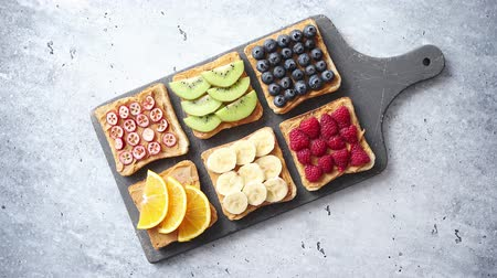 fıstık : Healthy breakfast toasts. Wholegrain bread slices with peanut butter and various fruits. Served on grey cutting board. Top view, grey stone background. Dieting concept Stok Video