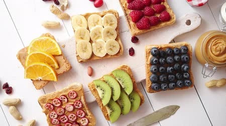 тост : Assortment of healthy fresh breakfast toasts. Bread slices with peanut butter and various fruits and ingredients on side. Placed on white wooden table. Top view, with copy space.